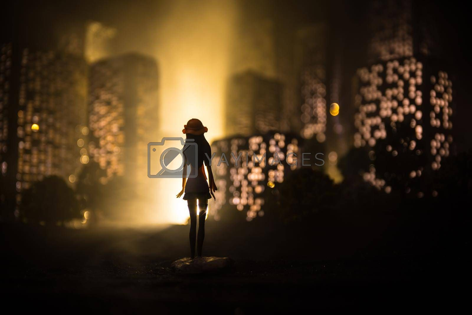 Cartoon style city buildings. Realistic city building miniatures with lights. background. Girl looking on night city. Selective focus