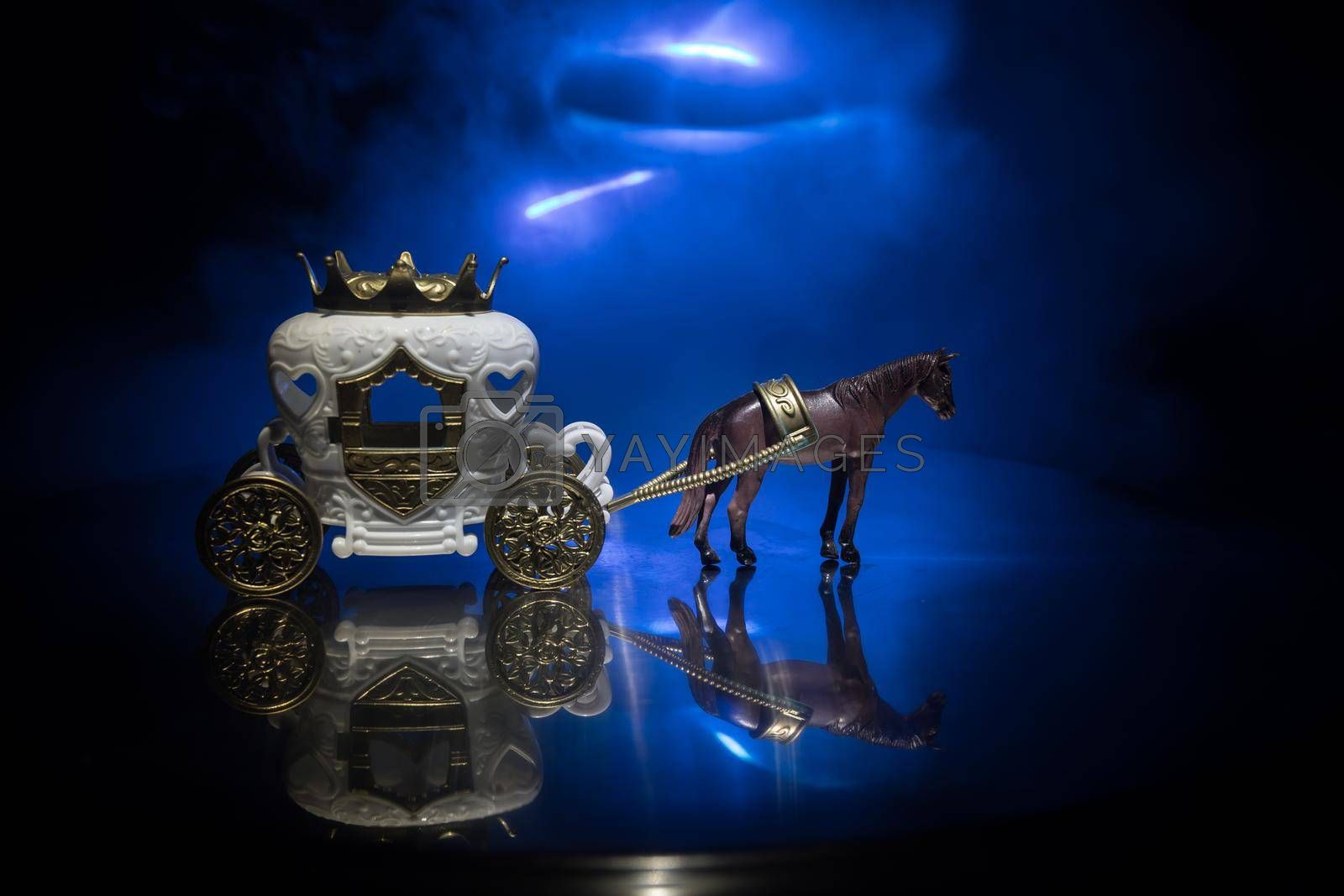 Little carriage with horse miniature on table. Creative decoration on dark toned foggy background. Selective focus