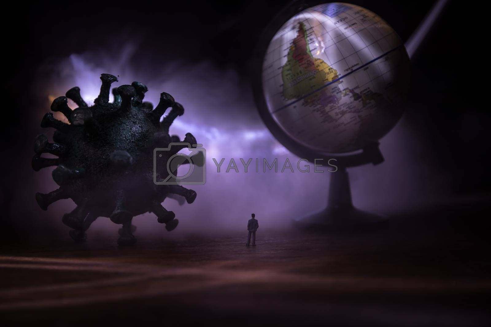 Corona virus global pandemic concept. Miniature man standing near big Corona virus novel in dark. Creative decoration with fog and backlight. Selective focus