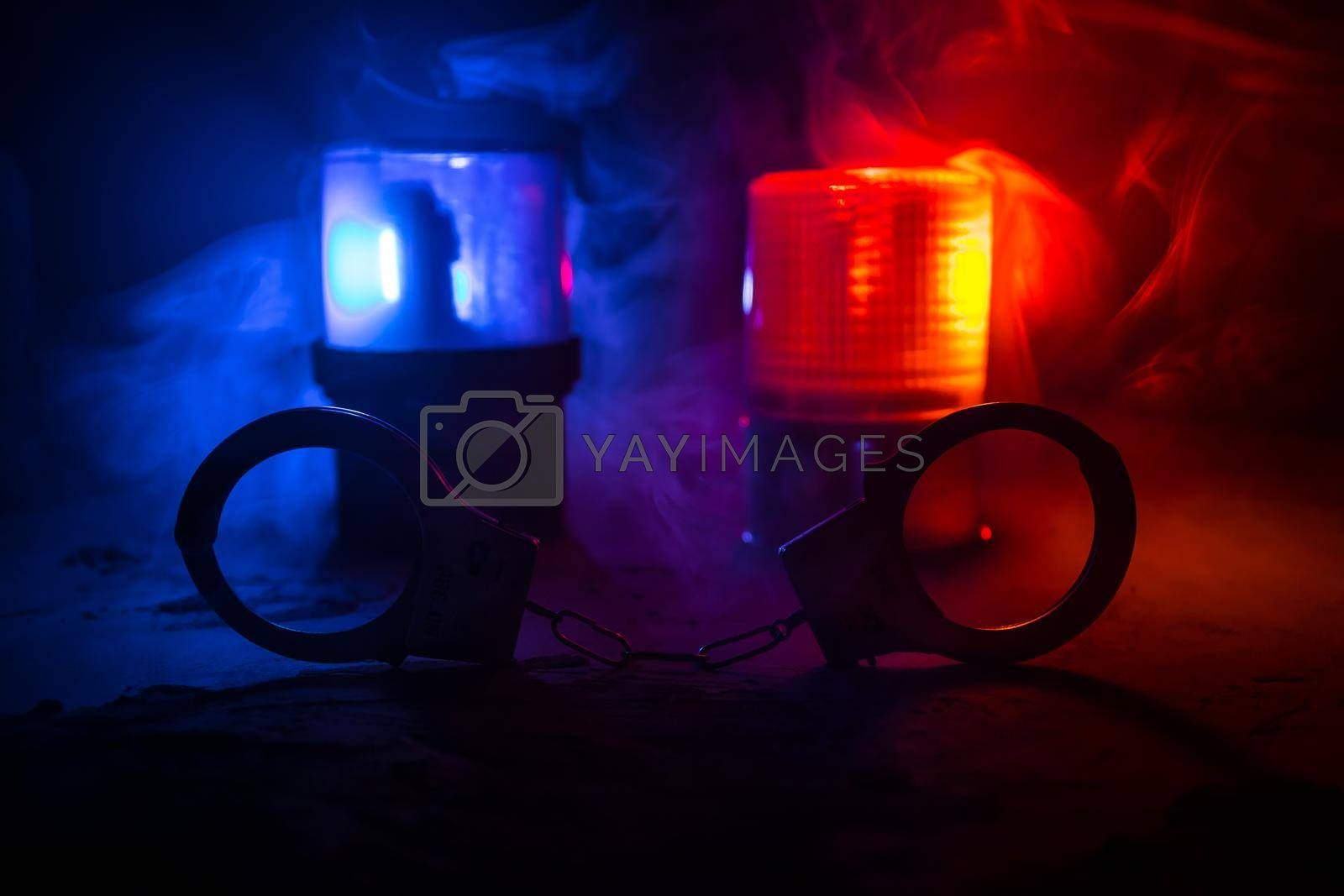 Police raid at night and you are under arrest concept. Silhouette of handcuffs with flashing red and blue police lights at foggy background. Selective focus