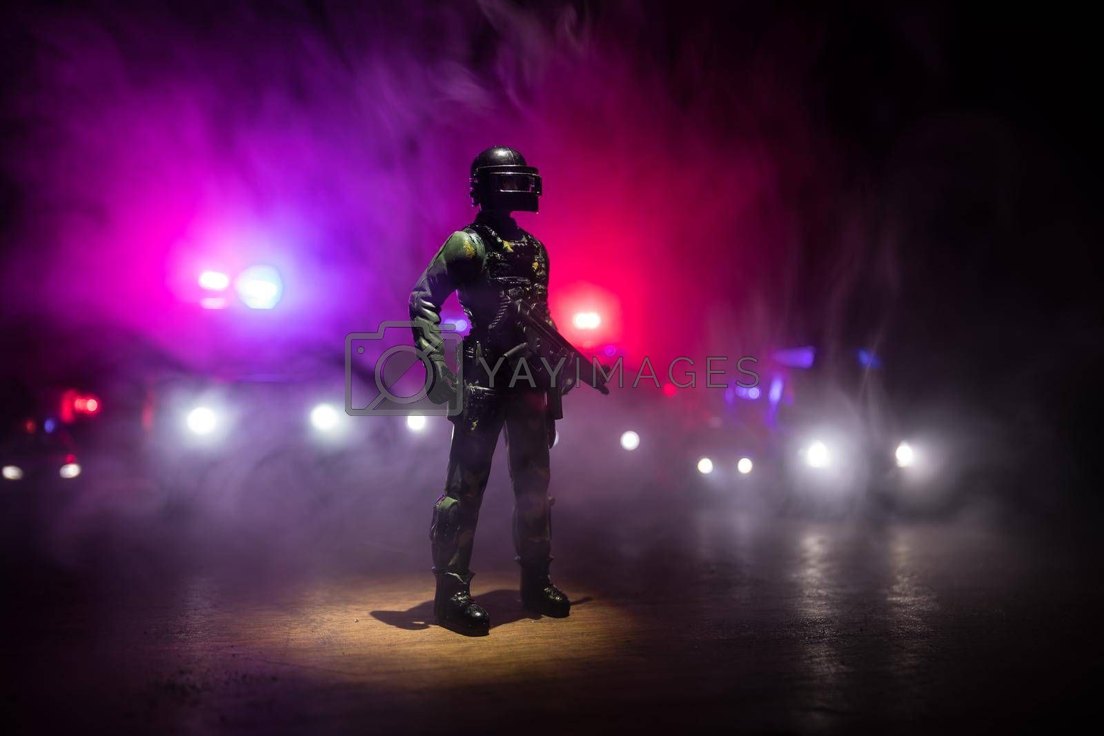 Anti-riot police give signal to be ready. Government power concept. Spec ops police in action. Smoke on a dark background with lights. Blue red flashing sirens. Selective focus