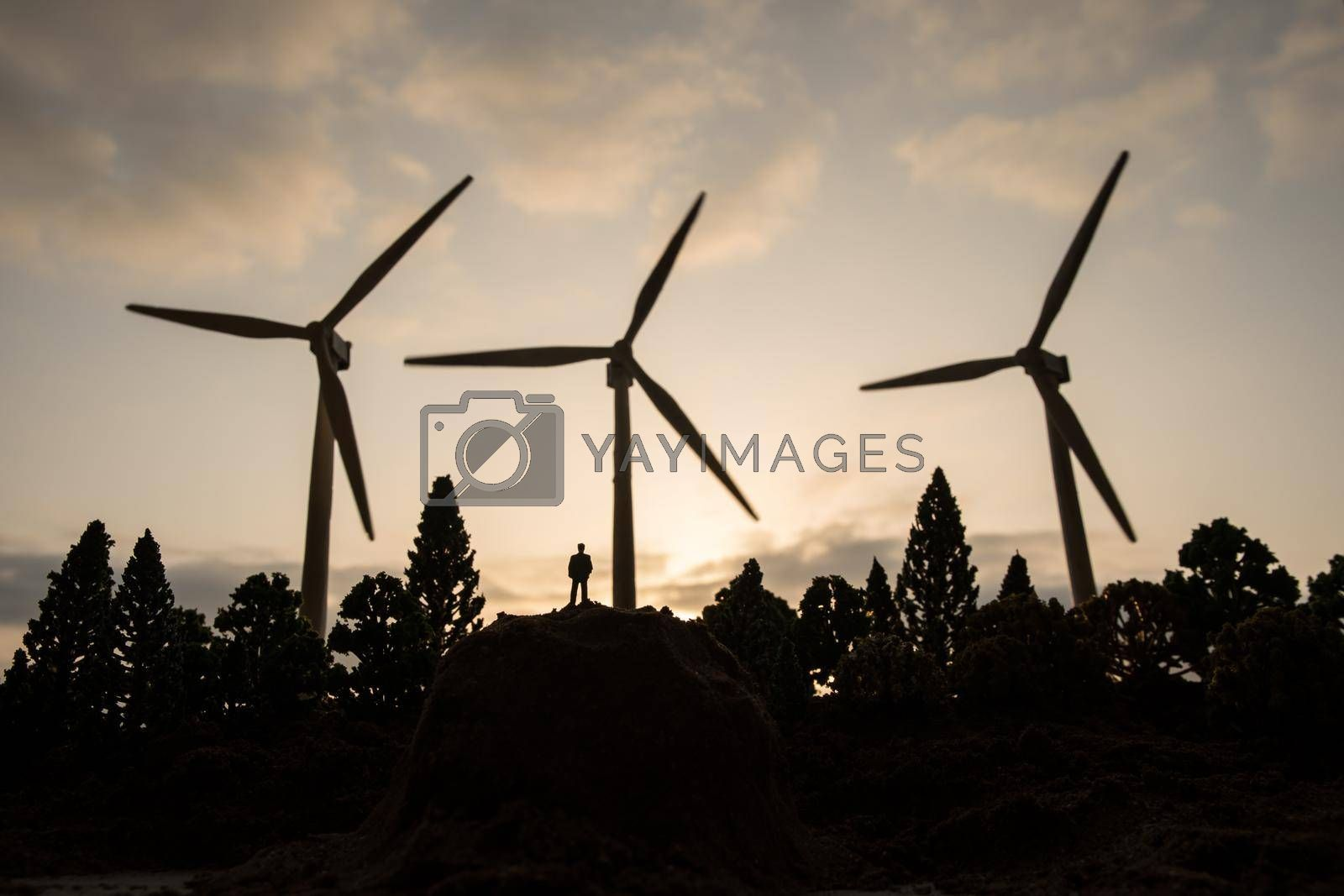 Electricity power in nature or clean energy concept. Wind Turbine producing alternative energy at sunset. Creative decoration with small miniature. Selective focus