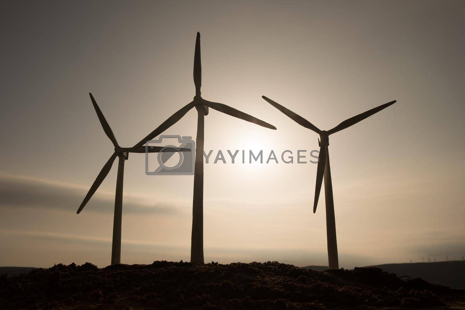 Electricity power in nature or clean energy concept. Wind Turbine producing alternative energy on hill during sunset time. Creative decoration with small miniature. Selective focus
