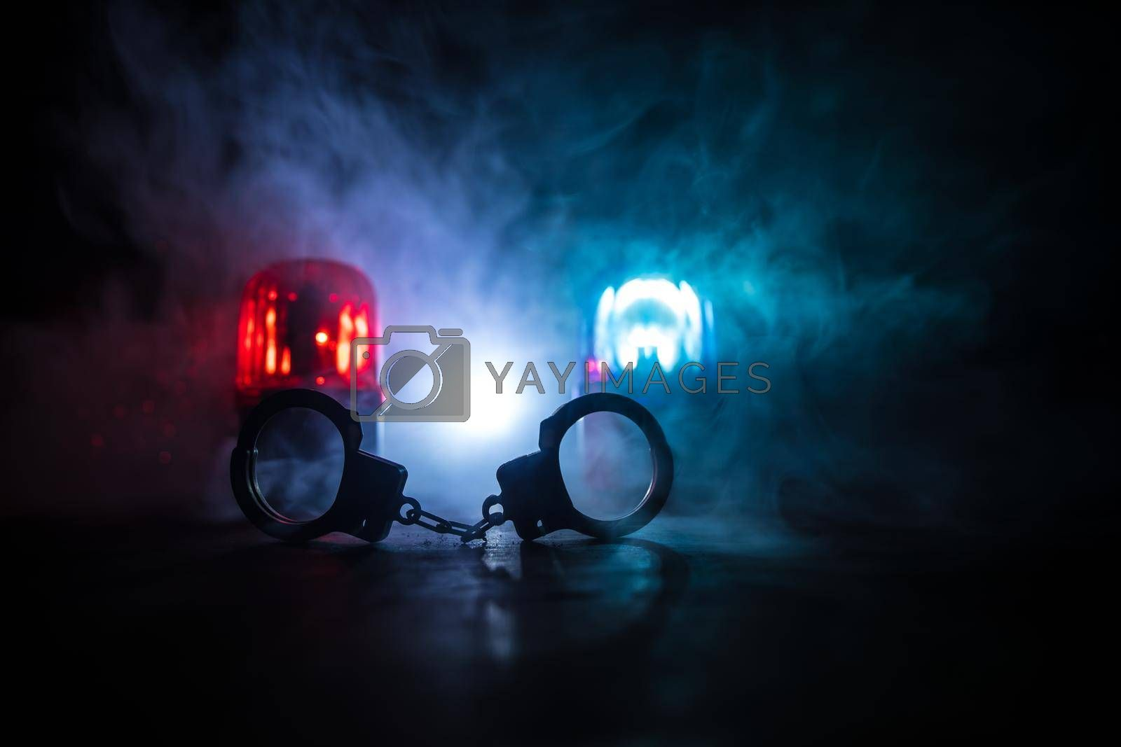 Police raid at night and you are under arrest concept. Silhouette of handcuffs with police car on backside. Image with the flashing red and blue police lights at foggy background. Selective focus