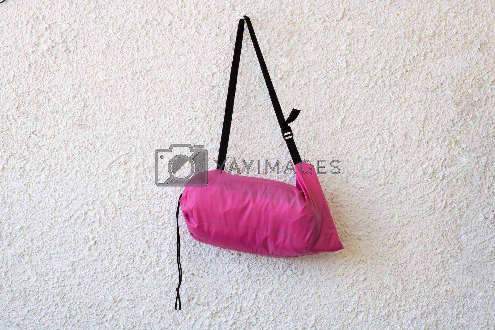 Pink sports bag with a black belt on a white rough background.