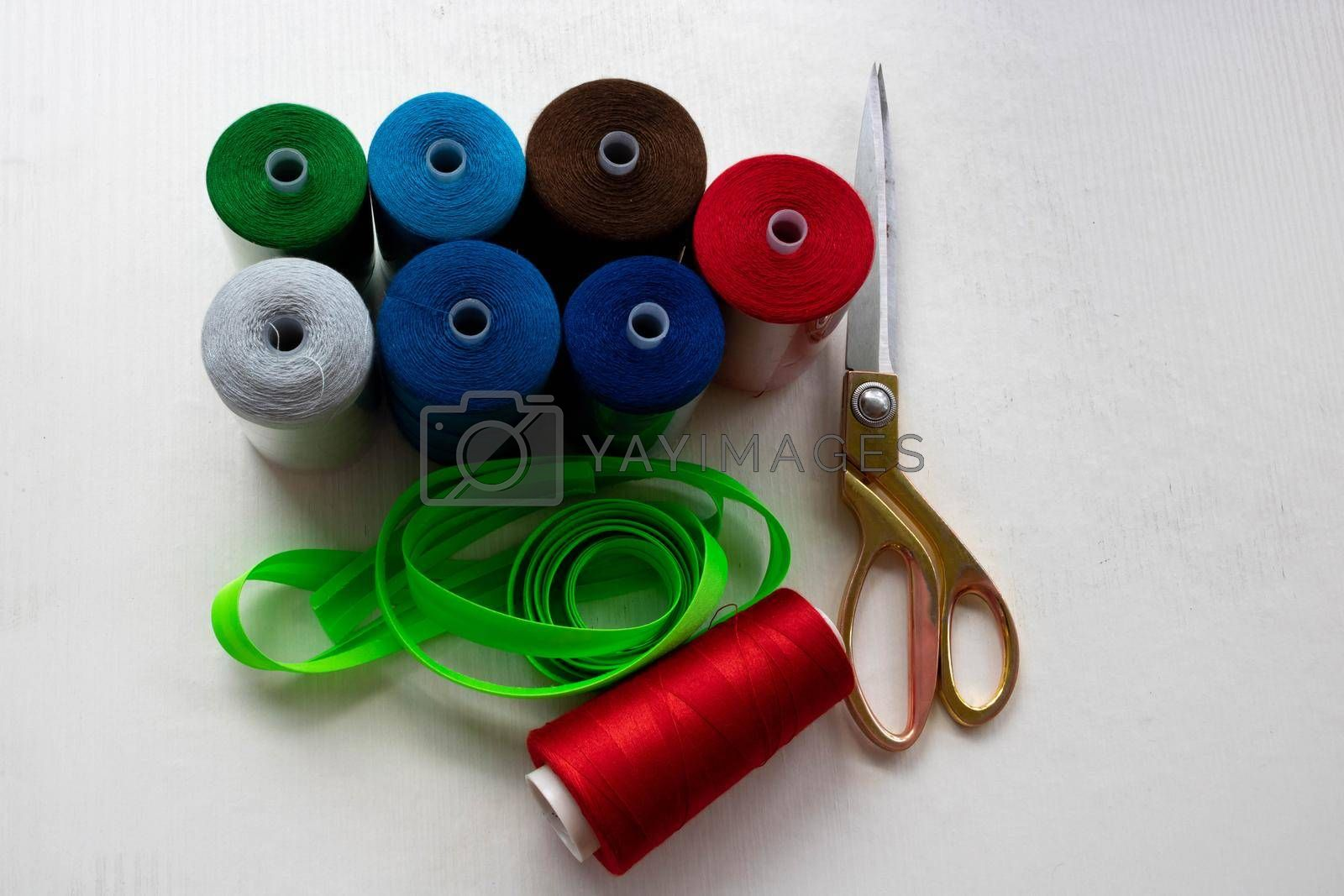 Colorful threads and scissors on a white background.