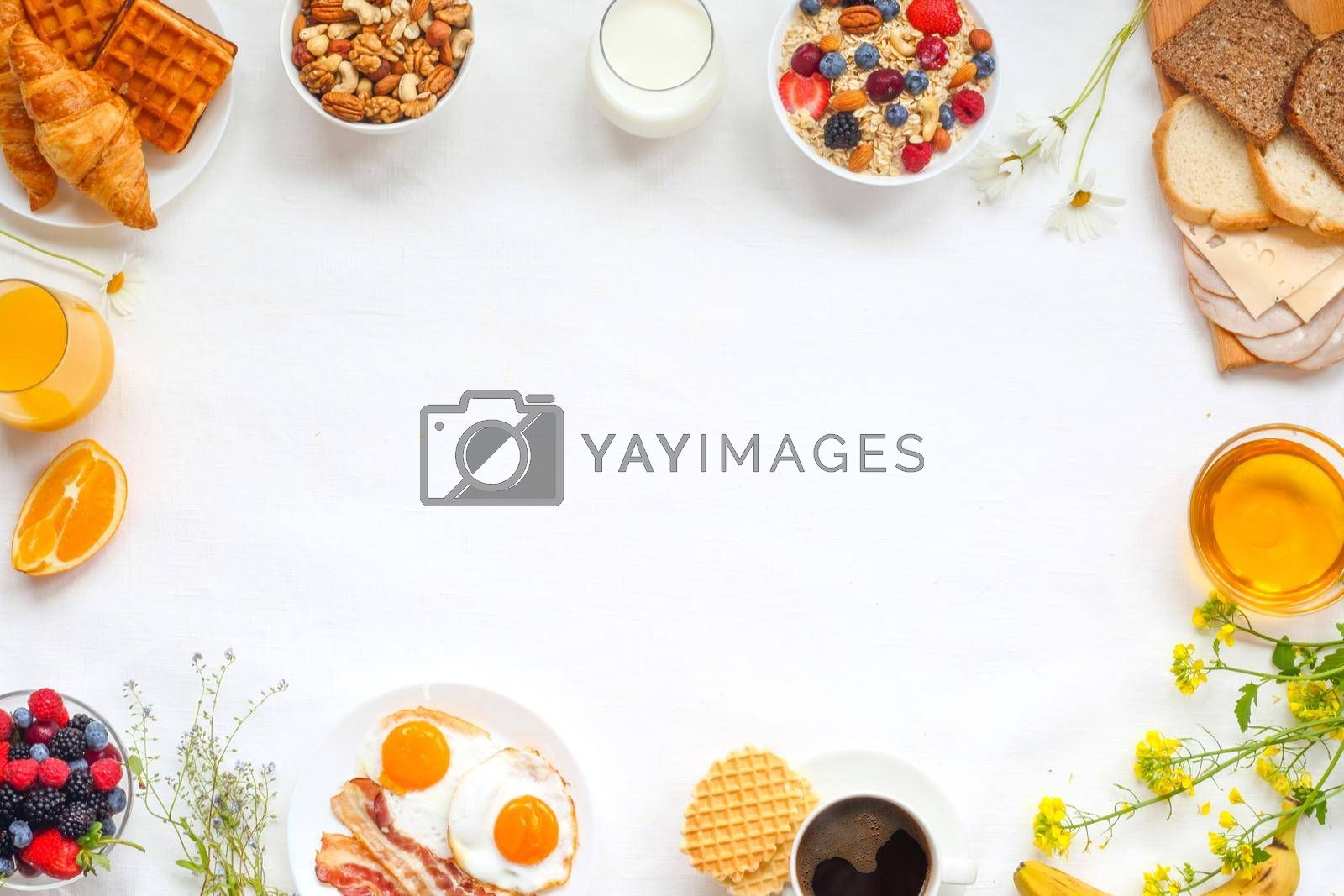 Healthy breakfast with muesli, fruits, berries, nuts, coffee, eggs, honey, oat grains and other on white background. Flat lay, top view, copy space for text, frame