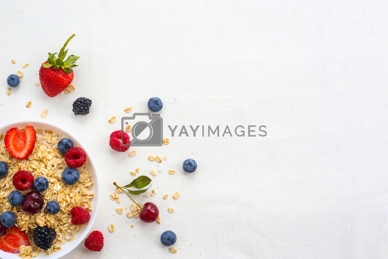 Oatmeal porridge in bowl topped with fresh berries, and homemade crunchy granola