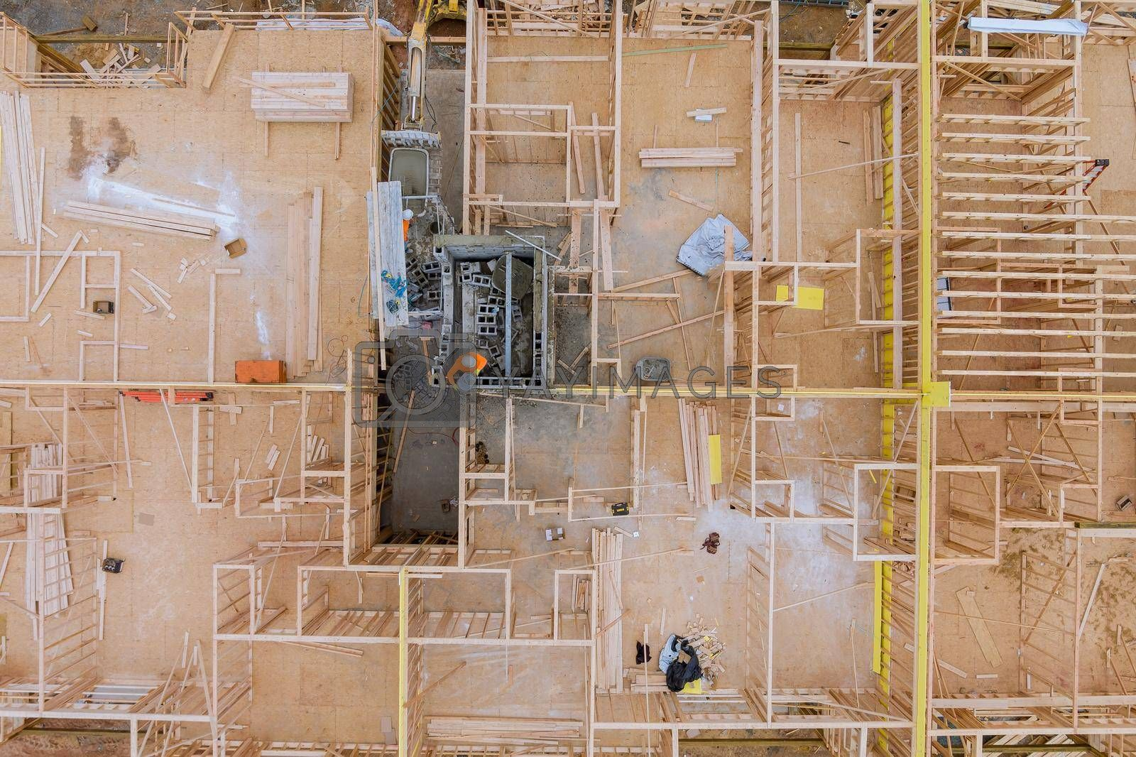 Aerial view of elevator shaft for concrete block building under construction work on workers are laying blocks the a beams house residential under construction