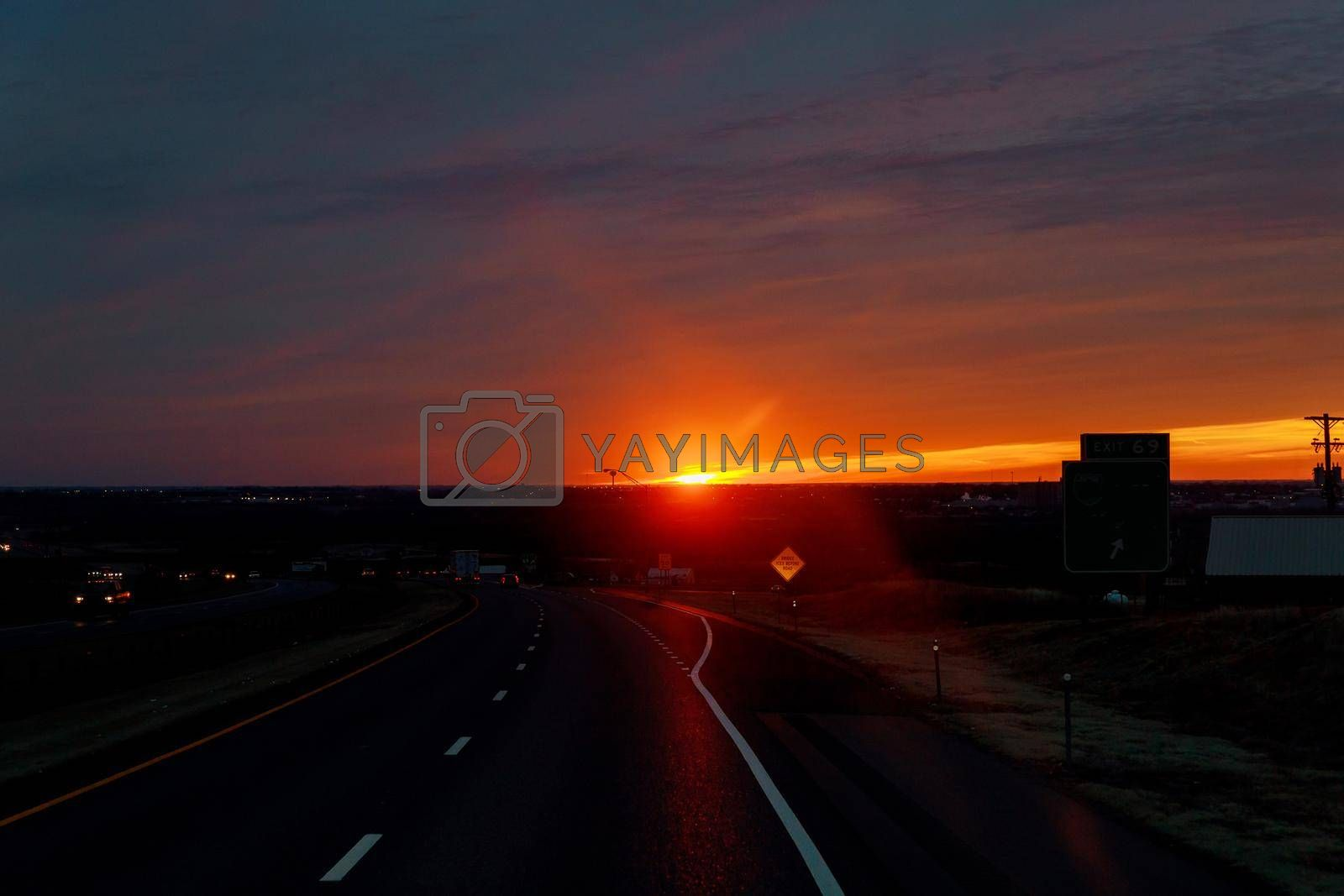 Country road with cloudy sky in the light of the dawn sunset car driving on highway