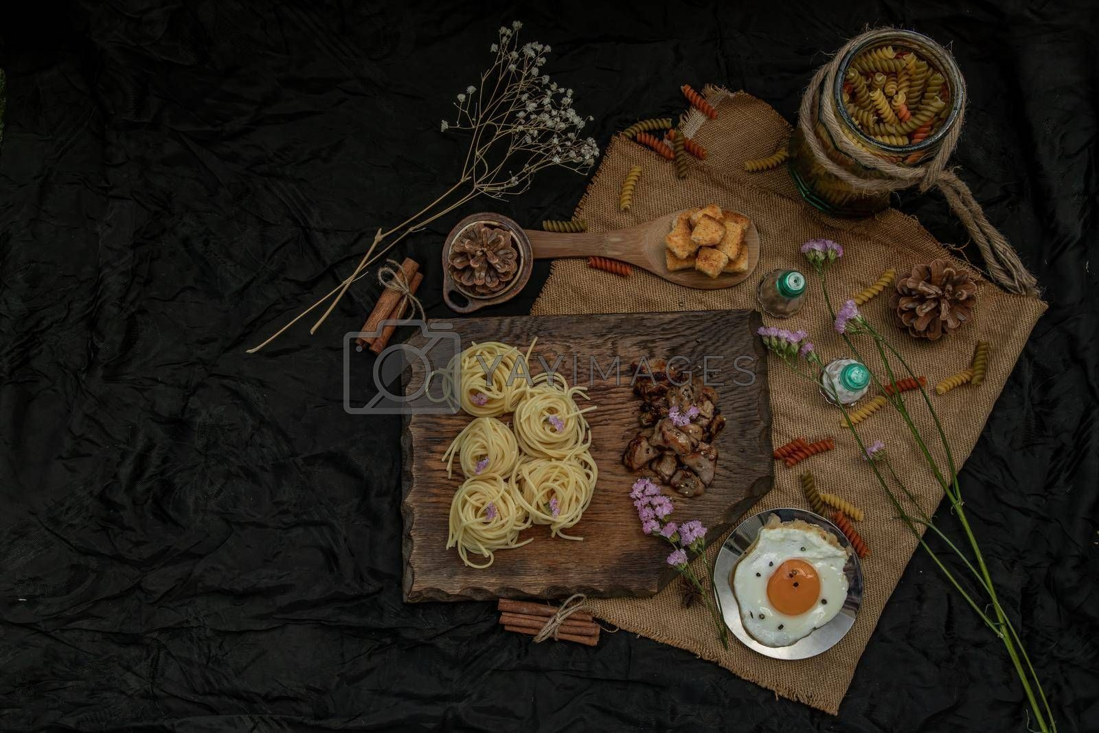 Royalty free image of Spaghetti with Roasted Chicken with Black Pepper on a wooden plate Served with Fried Egg and Crispy butter toast. by tosirikul
