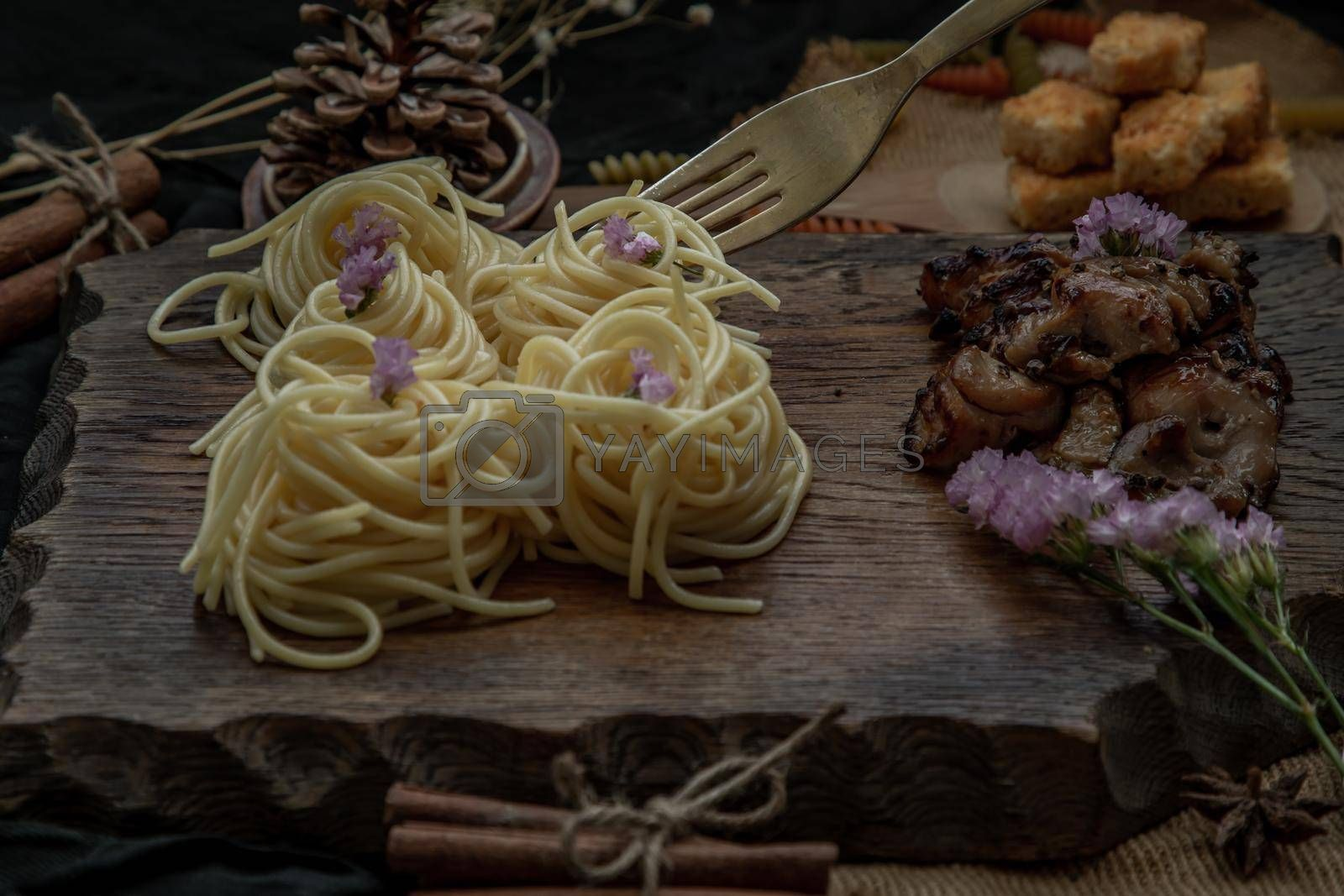 Royalty free image of Spaghetti with Roasted Chicken with Black Pepper on a wooden plate Served with Crispy butter toast. by tosirikul