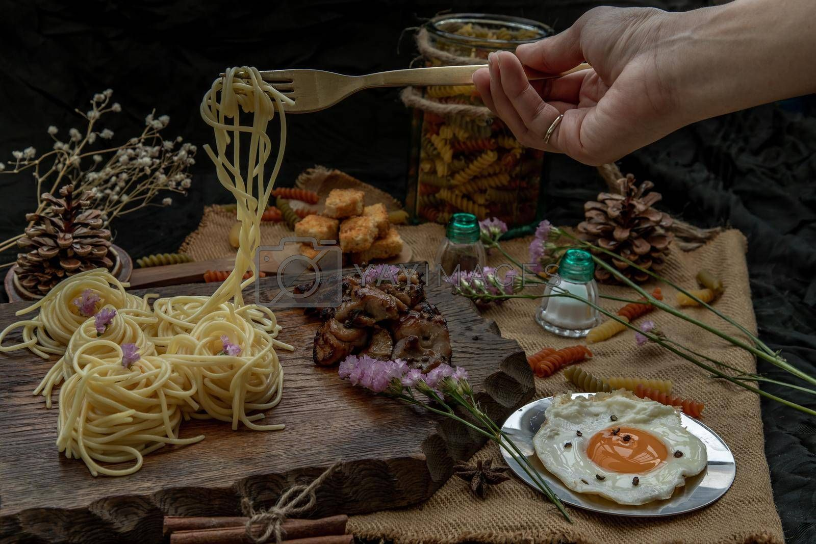 Royalty free image of Spaghetti with Roasted Chicken with Black Pepper on a wooden plate Served with Fried Egg and and Crispy butter toast. by tosirikul