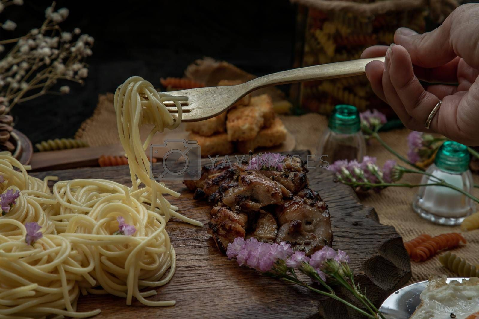 Spaghetti with Roasted Chicken with Black Pepper on a wooden plate Served with Crispy butter toast. Selective Focus.