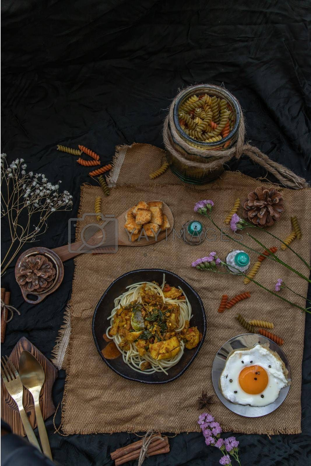 Royalty free image of Spaghetti topped with Stir fried spicy snapper on a brown plate Served with Fried Egg and Crispy butter toast. by tosirikul