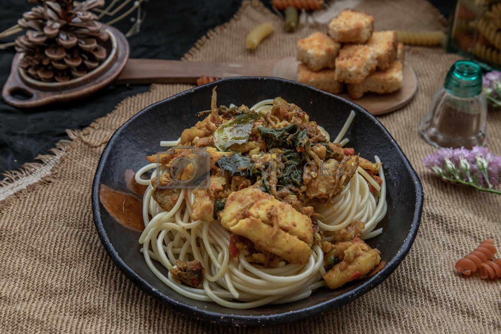 Royalty free image of Spaghetti topped with Stir fried spicy snapper on a brown plate Served with Crispy butter toast. by tosirikul