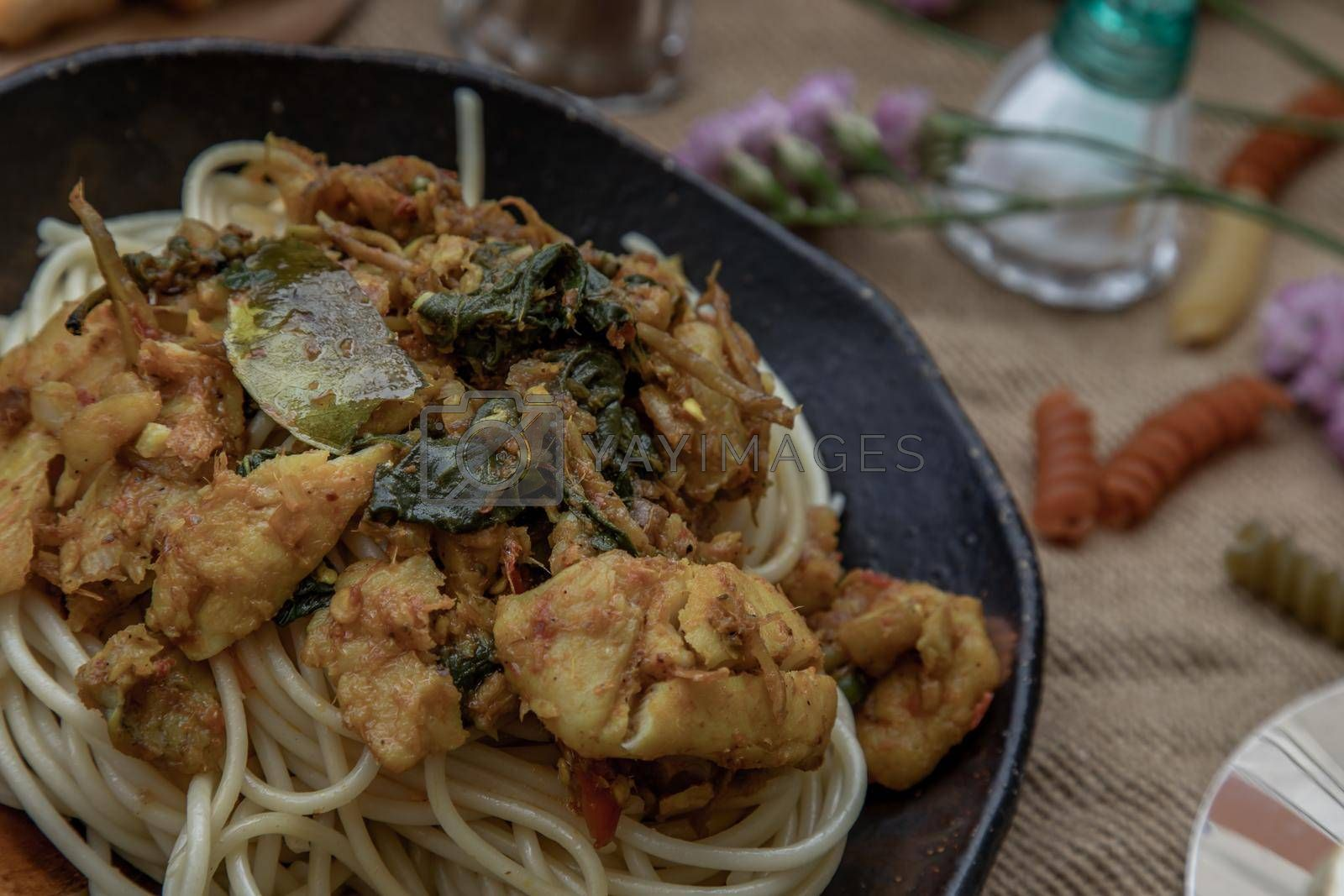 Close-up of Spaghetti topped with Stir fried spicy snapper on a brown plate. Selective Focus.