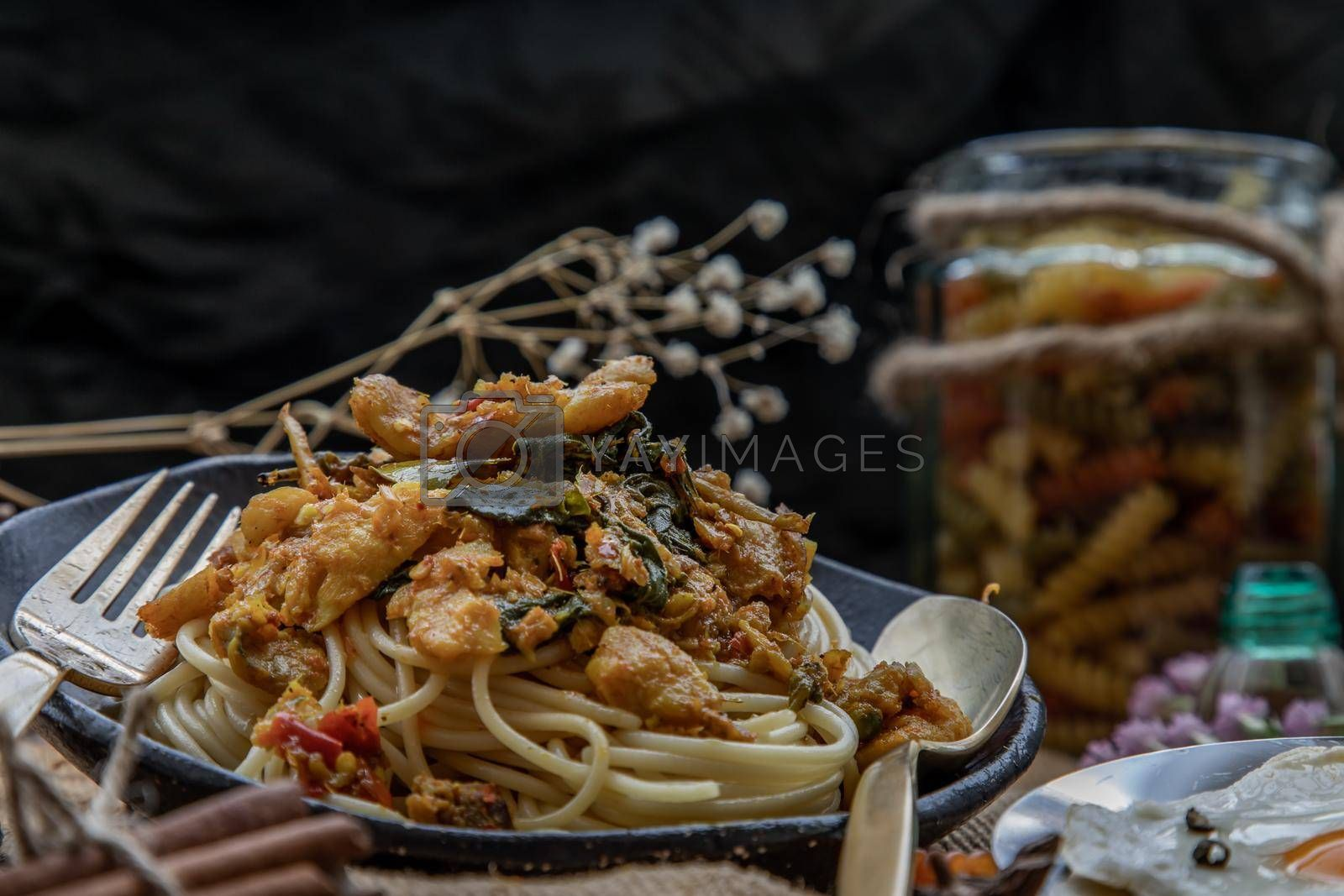 Royalty free image of Close-up of Spaghetti topped with Stir fried spicy snapper on a brown plate. by tosirikul