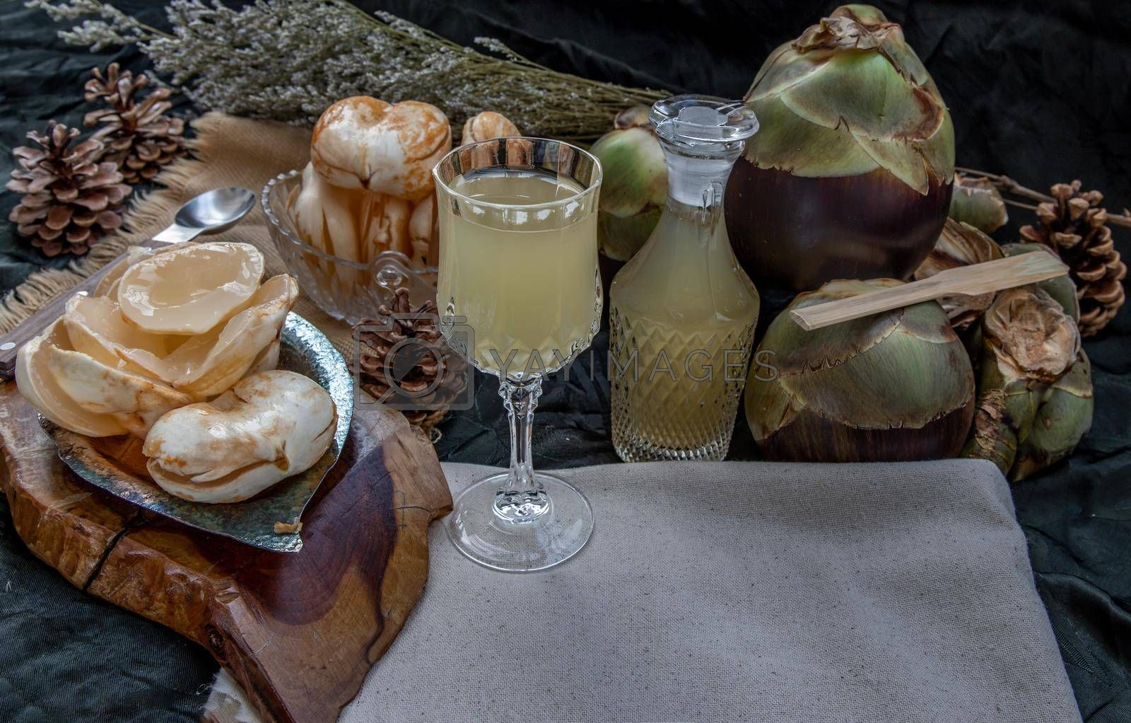 Royalty free image of Fresh toddy palm juice and Peel toddy palm at front of dark background. by tosirikul