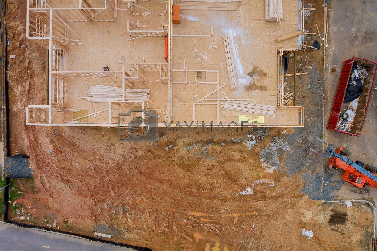Aerial view of apartment framing of a new house under construction with forklift stacker wooden boards the trash dumpsters construction