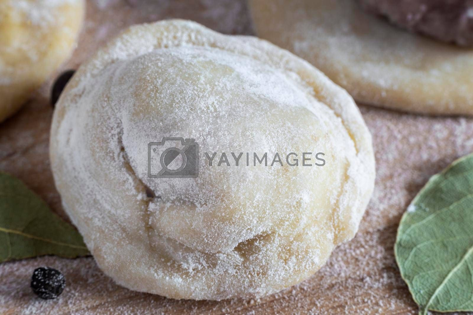 Cooking homemade dumplings, Russian dumplings with meat on a wooden table and ingredients for cooking. Rustic style. Front view, close-up