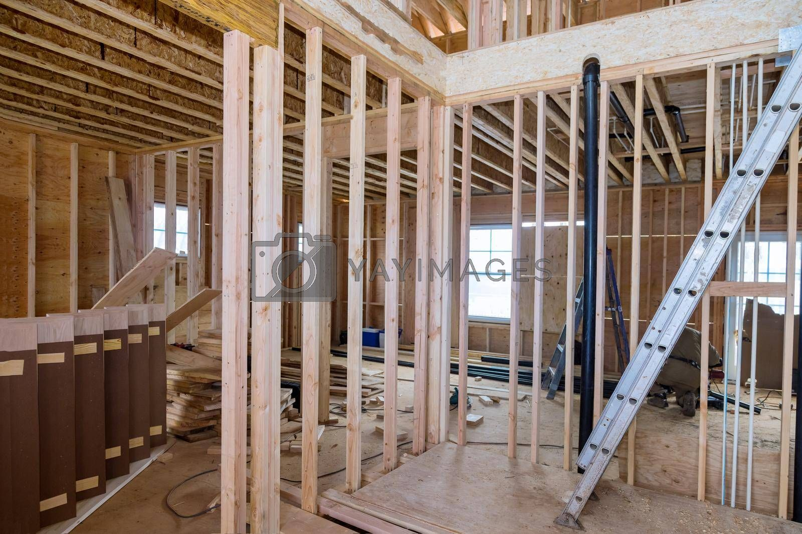Beams under construction framing of a new unfinished wooden house at a construction site
