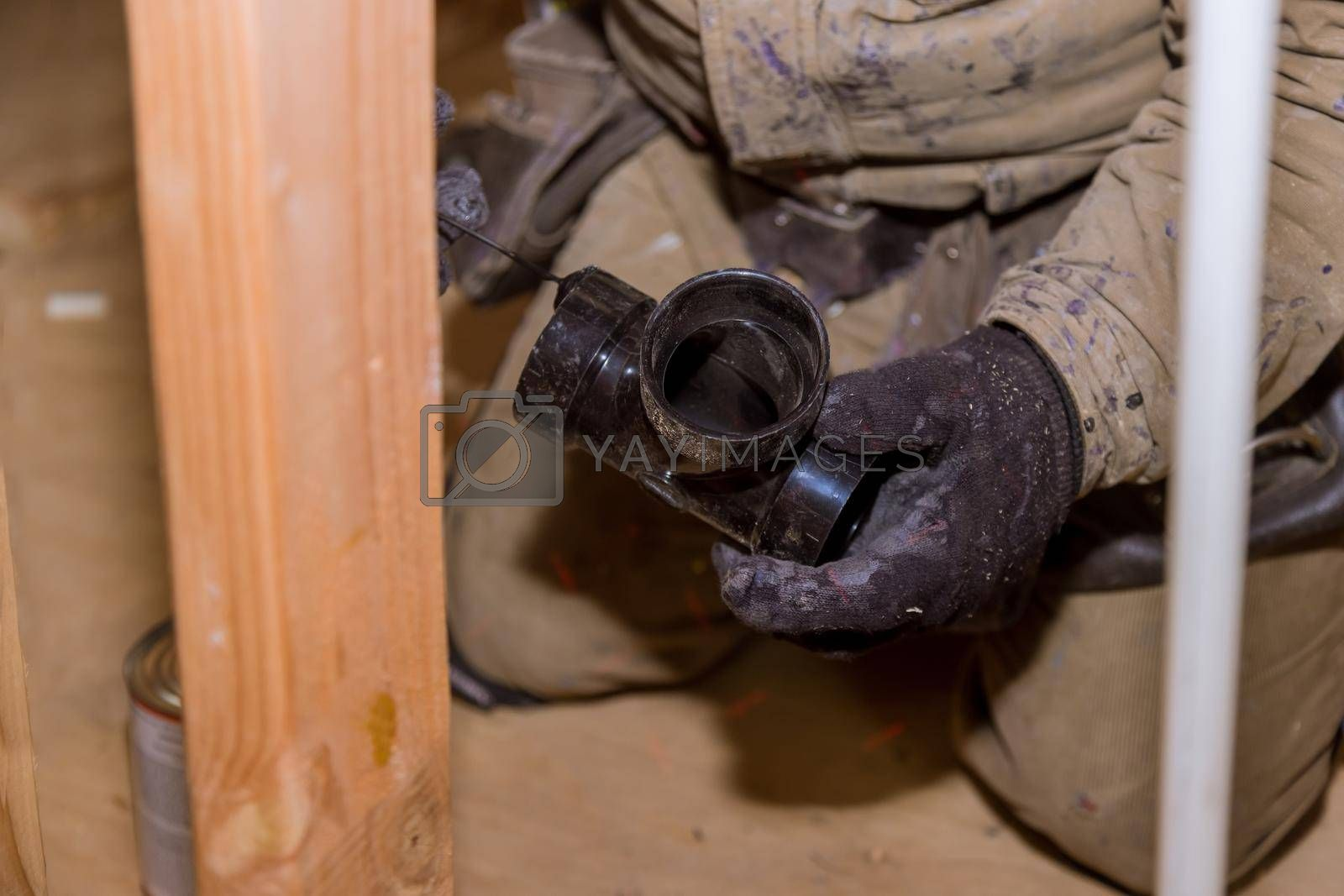 Plumbing contractor installing PVC plastic drain pipe in the section for a custom house