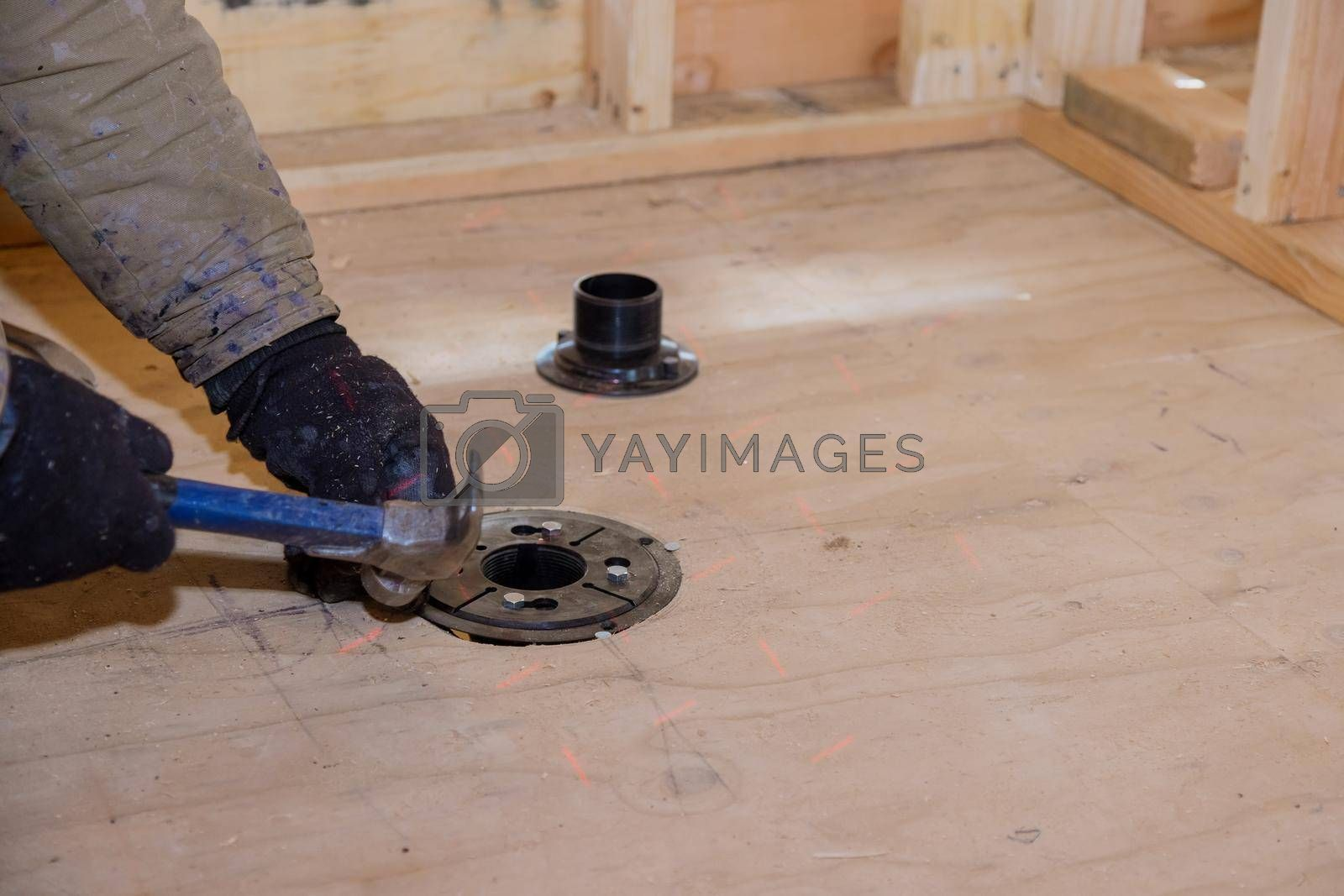 Nailing shower drain to plywood flooring for new plumbing install of supply sewage