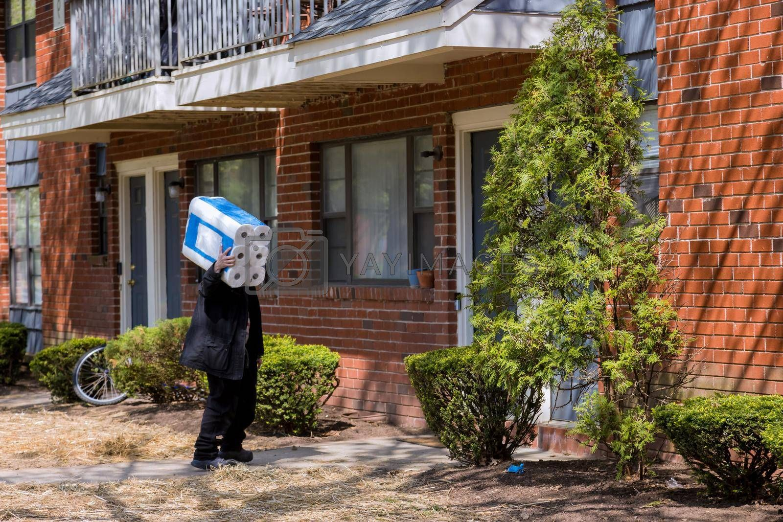 Man in his hands carries a large boxes package of rolls of toilet paper