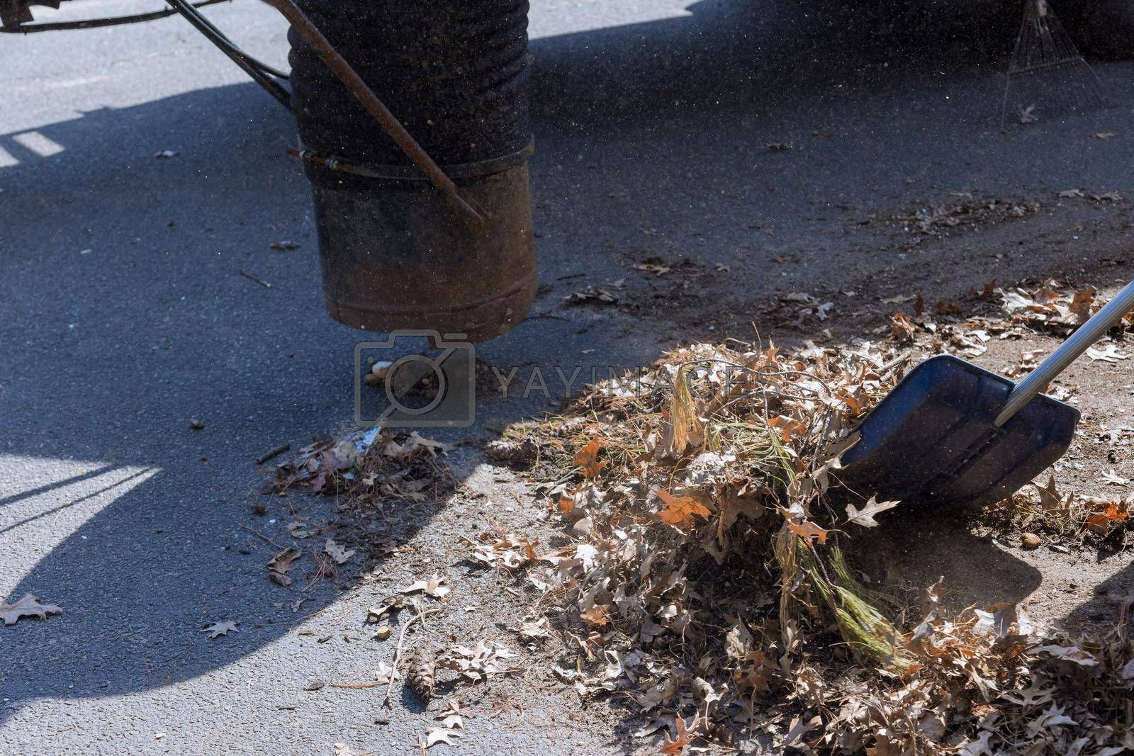 Outdoor manual worker clean the fallen leaves on vacuum up in the road by autumn