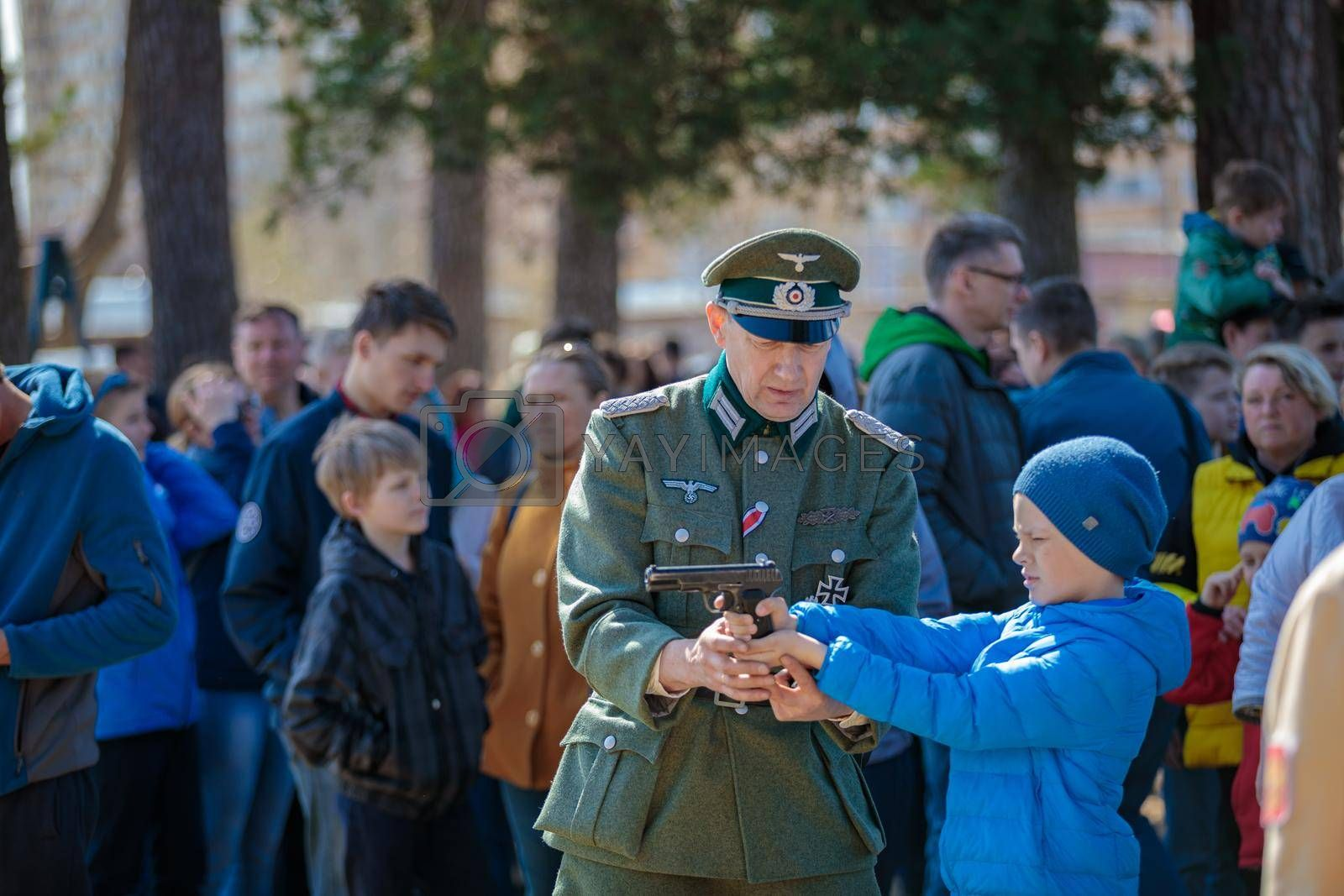 Reconstruction of the Second World War. A man in the uniform of a German officer shows a boy how to shoot a pistol. The Great Patriotic War. Liberation of Odessa. Zelenograd Russia April 18, 2021