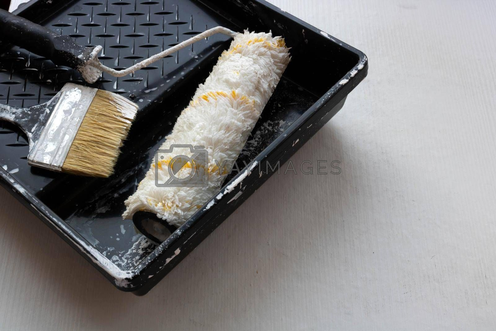 In a black tray on a white background are a brush and a roller for painting the walls. Repair concept.