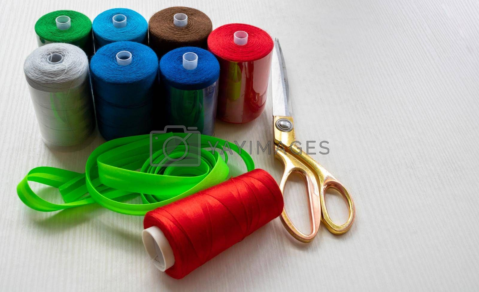 Colorful threads and scissors on a white background. Space for text