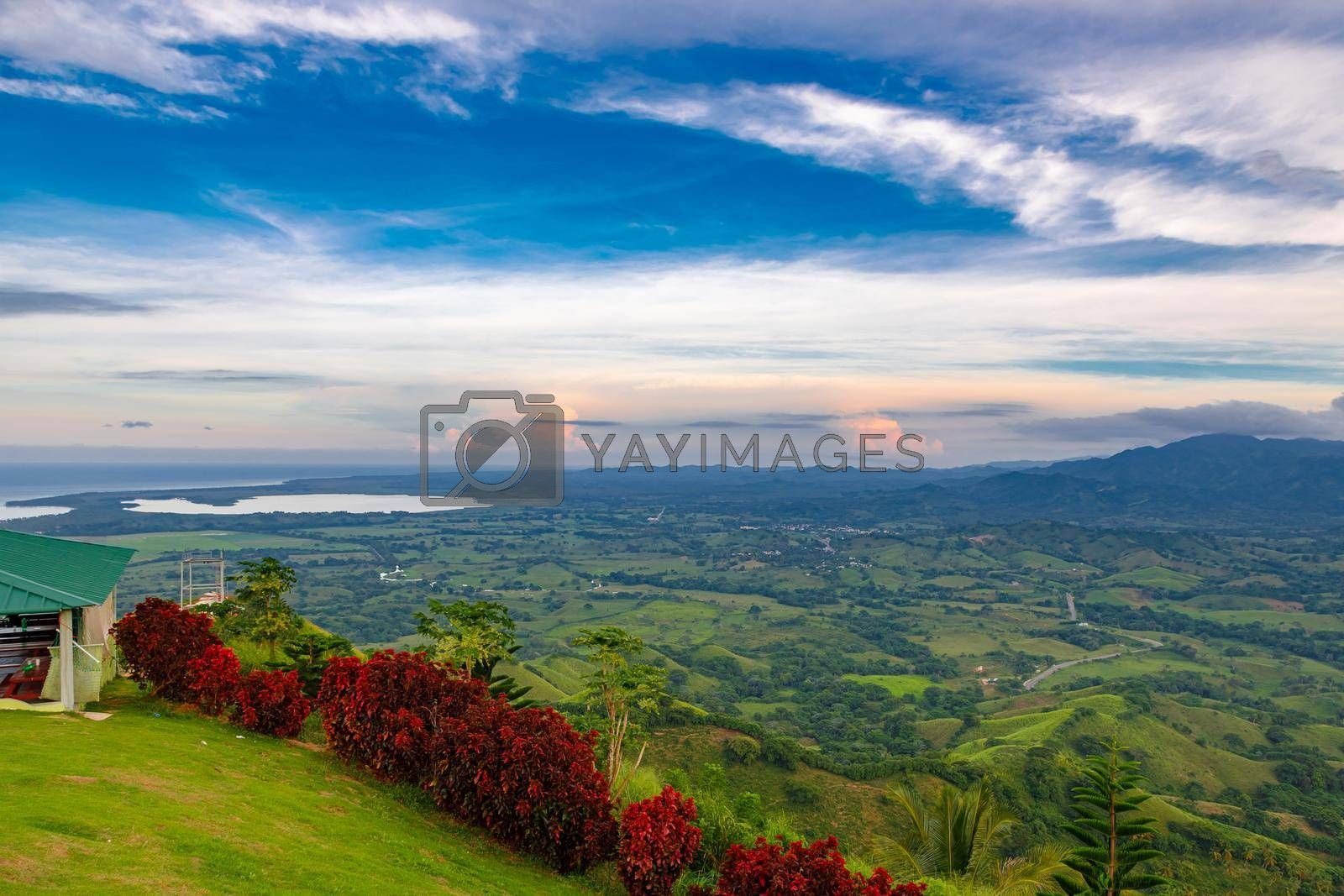 View from a large mountain to a valley with a lake in the Dominican Republic. Setting sun. Around greenery and red bushes