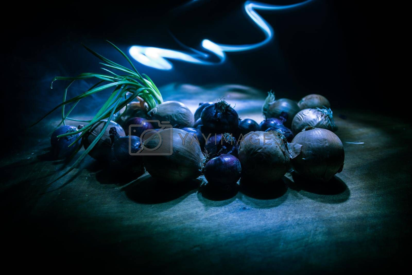 Vegetable concept. Different onions on wood in dark. Selective focus. Colorful background.
