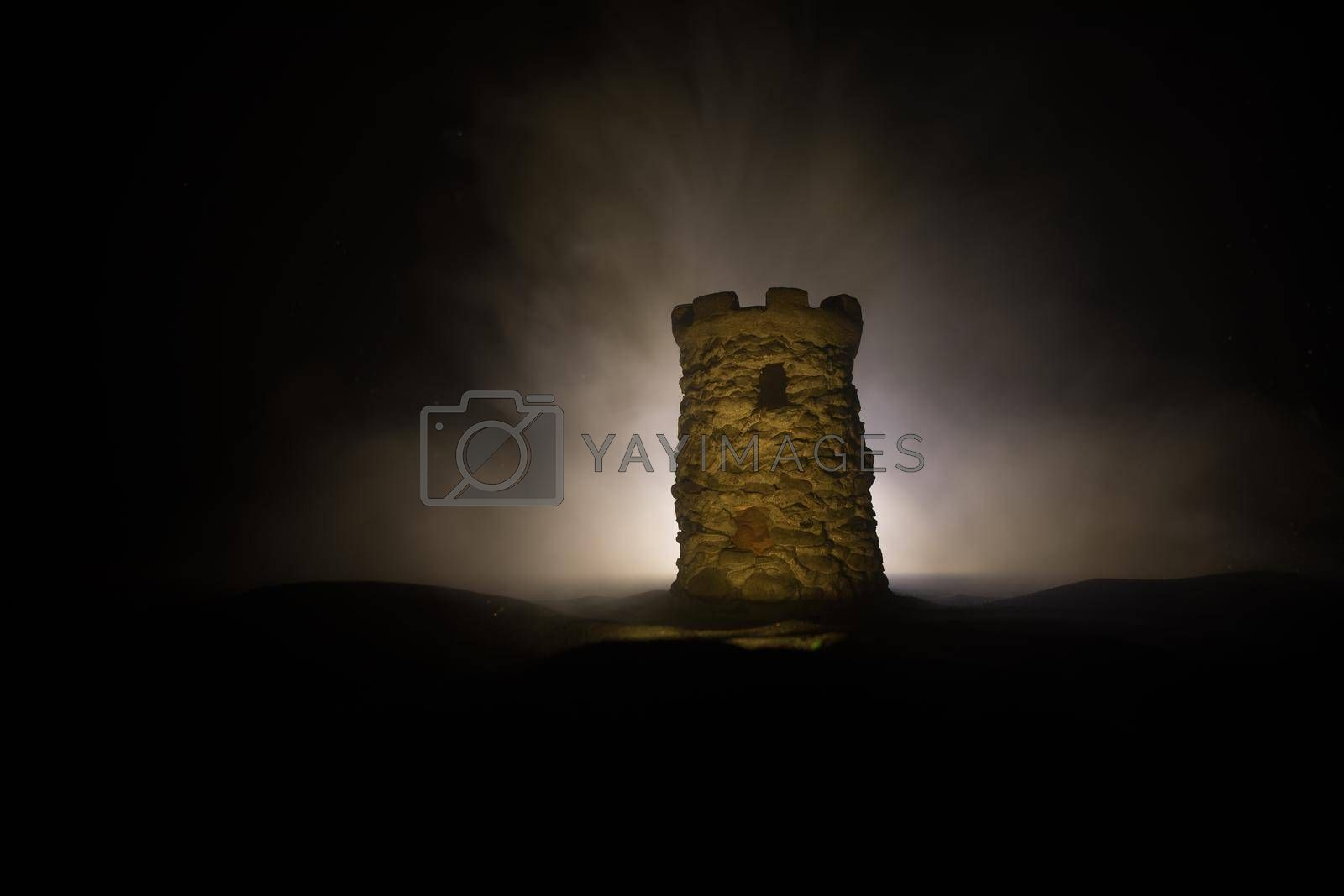Stone defence tower at night. Medieval castle miniature with toned foggy backlight. Creative table decoration. Selective focus