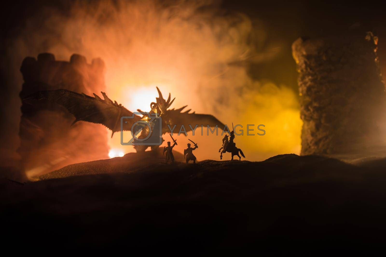Fantasy battle scene with dragons attacking a medieval castle at night. Battle between dragon and heroic soldiers. Creative table decoration. Selective focus