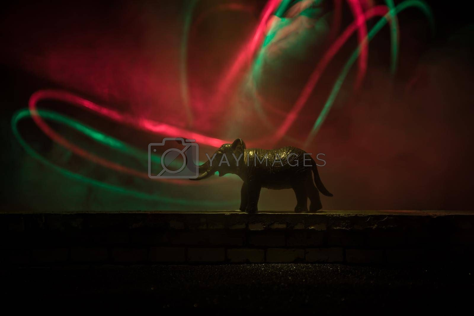 Silhouette of an elephant miniature standing at foggy night. Creative table decoration with colorful backlight with fog. Selective focus