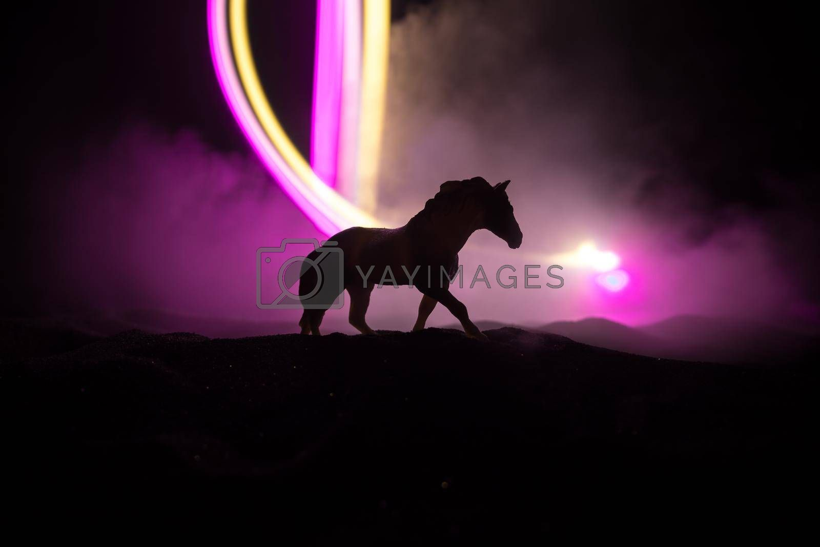 Silhouette of a horse miniature standing at foggy night. Creative table decoration with colorful backlight with fog. Selective focus