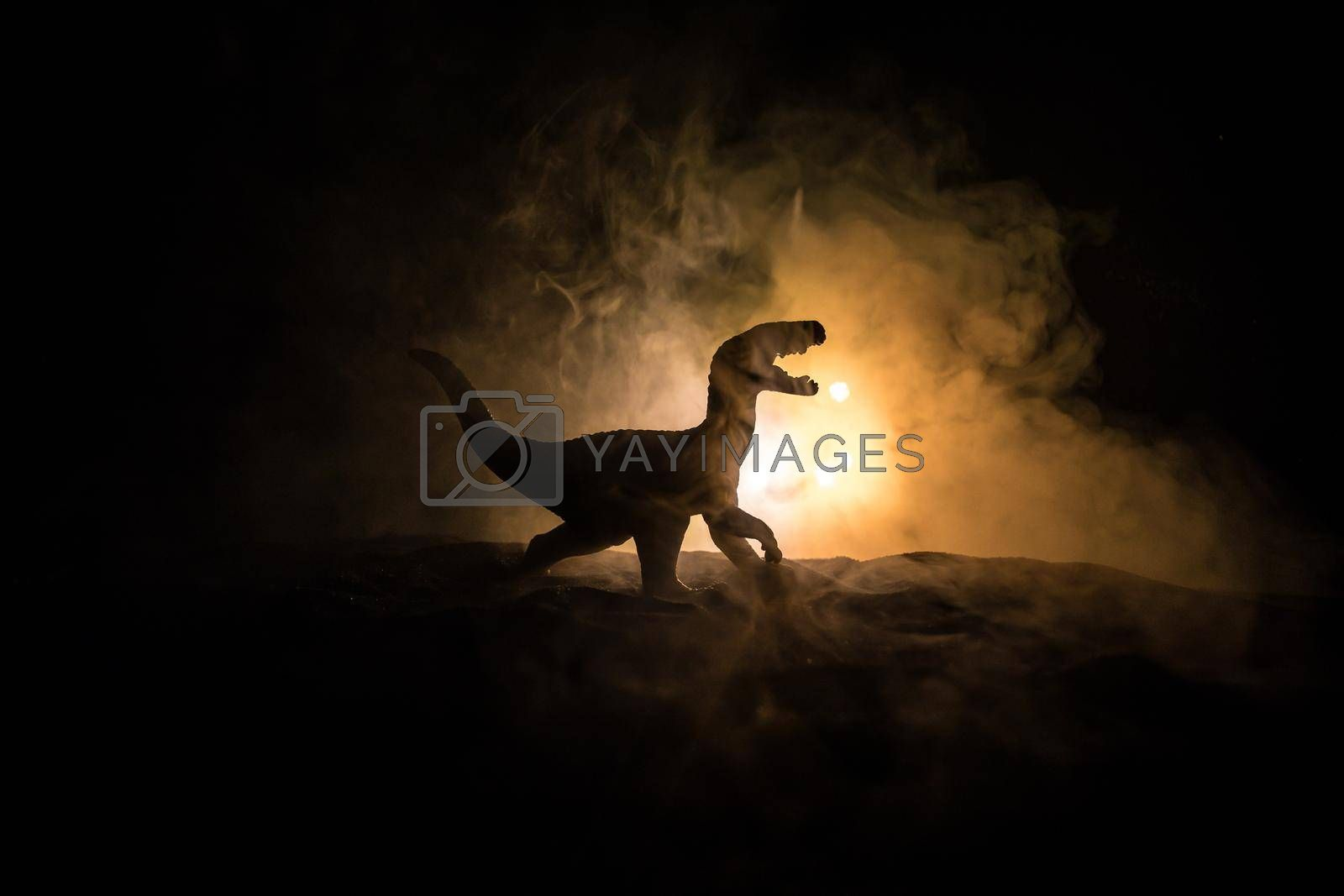 Silhouette of giant Dinosaur in foggy night. Creative decoration with little miniature. Burning misty background. Selective focus