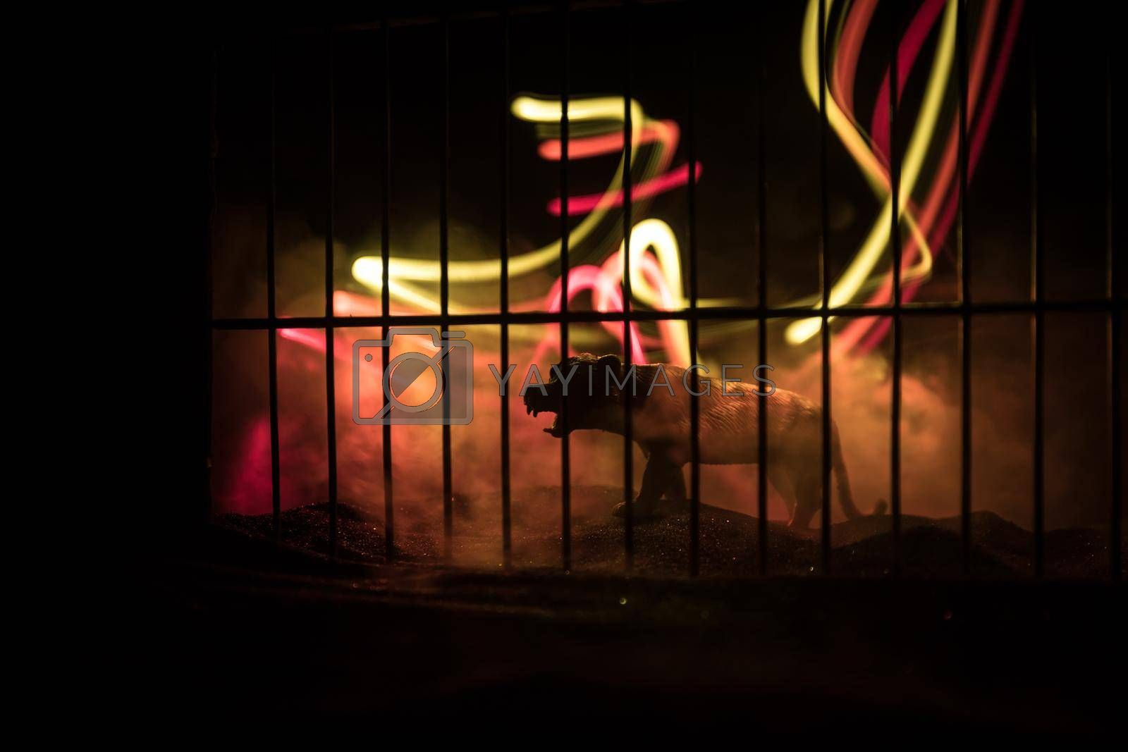 Silhouette of a tiger miniature standing in a zoo cage dreams of freedom. Creative decoration with colorful backlight with fog. Selective focus