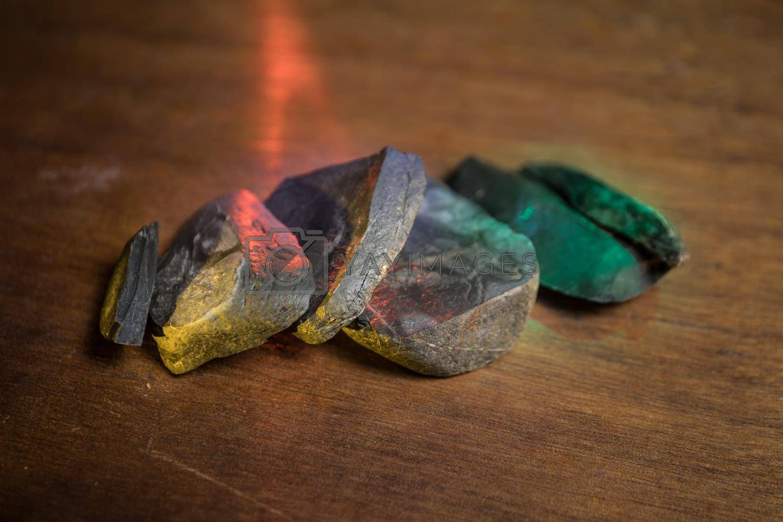 Parts of broken stone on a wooden table. Colorful lights on stones in selective focus. Close up