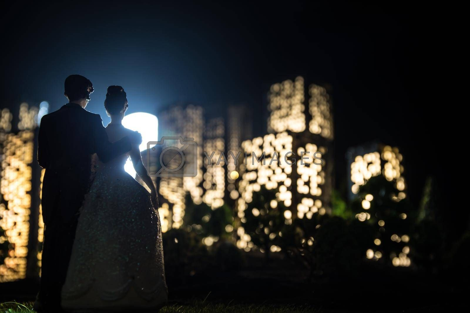 Cartoon style city buildings. Realistic city building miniatures with lights. background. Romantic couple silhouettes standing in from of nigth city in selective focus