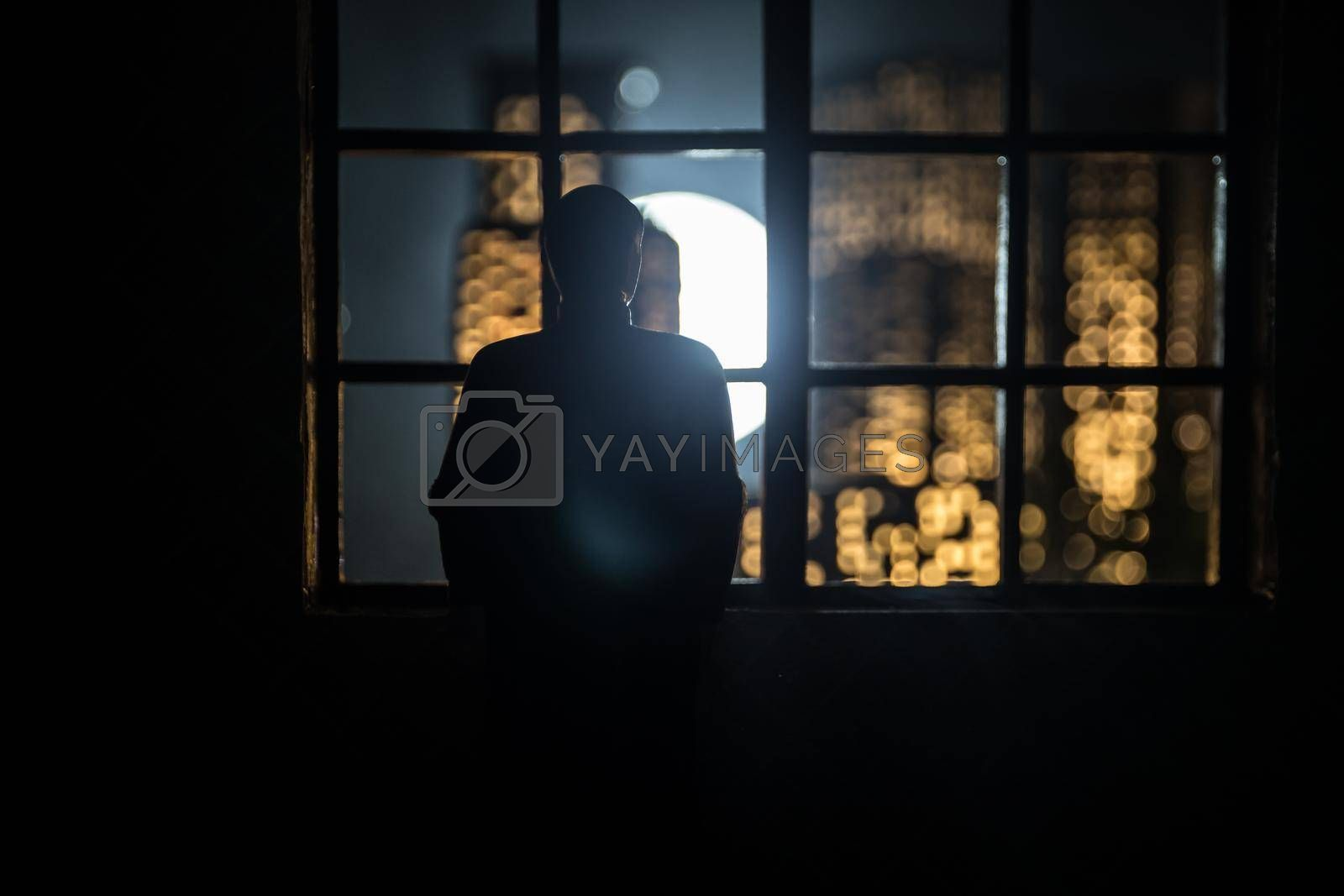 The silhouette of a man in front of a window with a view over a city lit in the night. Creative artwork decoration. Realistic dollhouse miniature. Selective focus