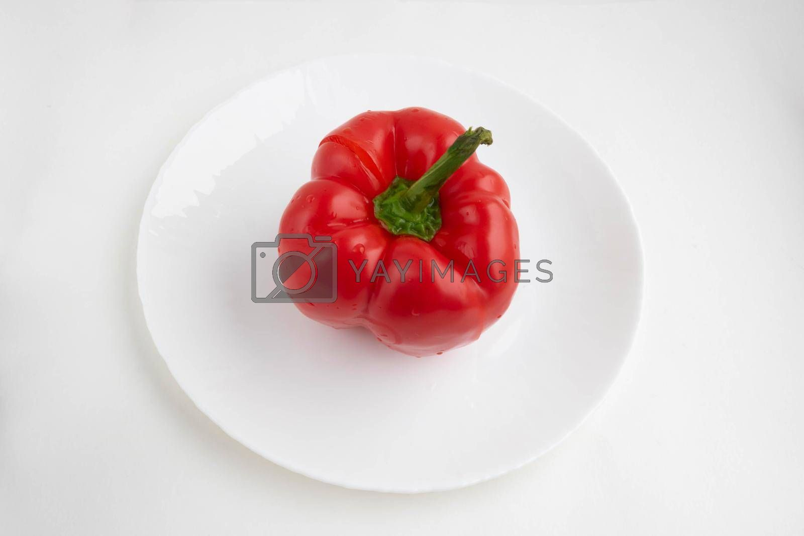 Red pepper on a white plate, isolated on a white background.