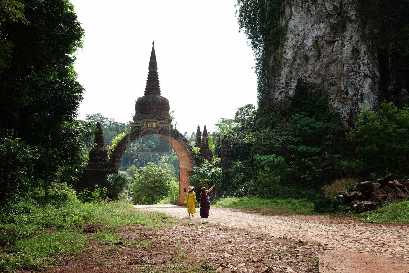 The scenery of the Khao Na Nai Luang Dharma Park or Phutthawadee arch with the orange flowers and green grass foreground at Surat Thani Province, Thailand.