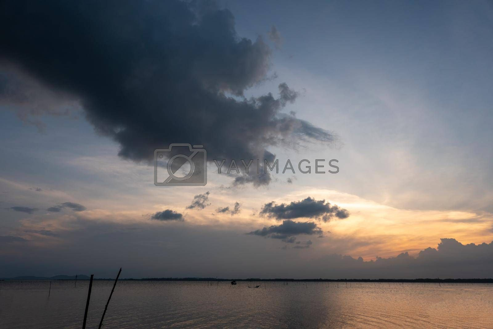Royalty free image of sunset over the sea with cloudy sky by chuanchai