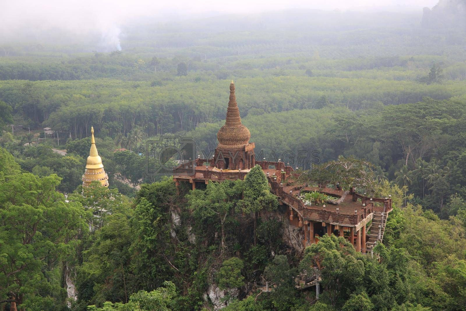 Royalty free image of Landscape of beautiful sunrise with pagoda on peak mountain and tree with misty morning at Na Nai Luang temple , Surat Thani Province, Southern of Thailand by chuanchai