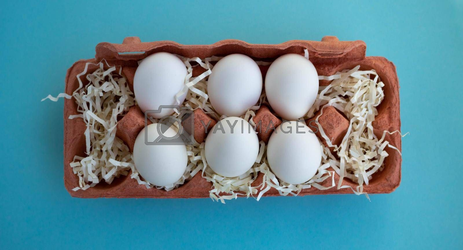 Six white fresh organic eggs in a beige eco-friendly cardboard egg container on a blue background. Easter concept, ecology, zero waste.