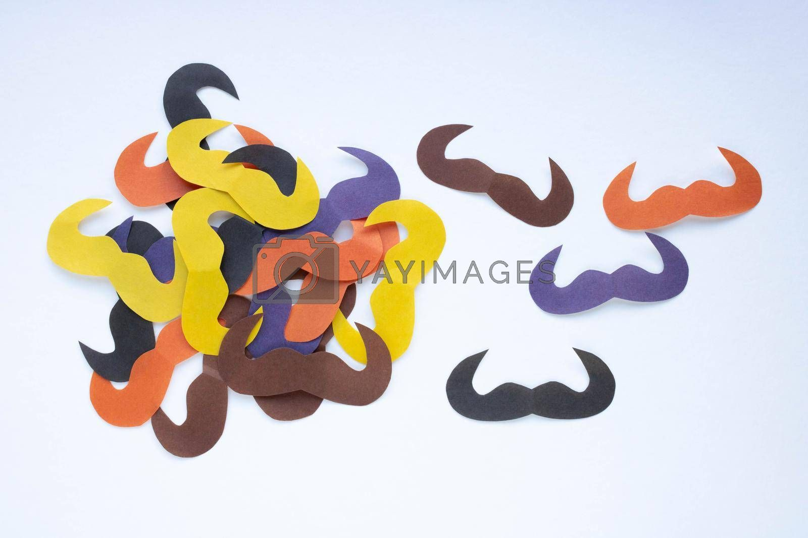 On a white background, there are many colorful paper mustaches. Father's Day, party decoration concept.